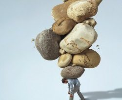 Man carrying large rocks on his back --- Image by © C.J. Burton/Corbis